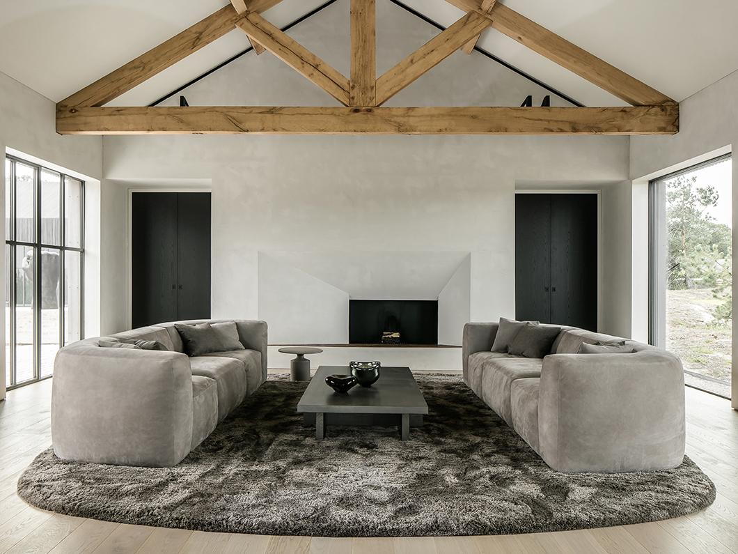 BO sofa, RAAF coffee table and carpet by Carpetlinq in living room with fireplace or hearth at office in Brabant, Netherlands