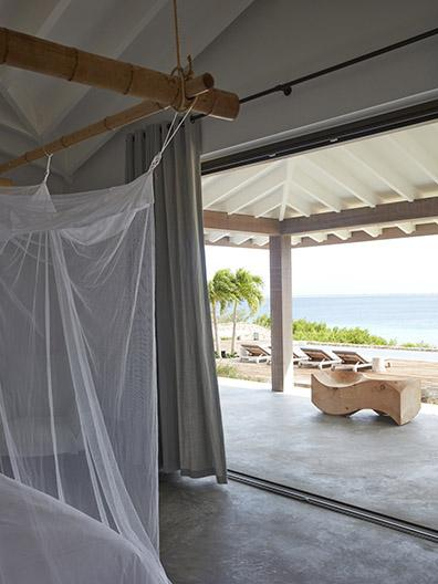 View at sea and GIJS daybeds / sunloungers from bedroom at beach villa on Bonaire